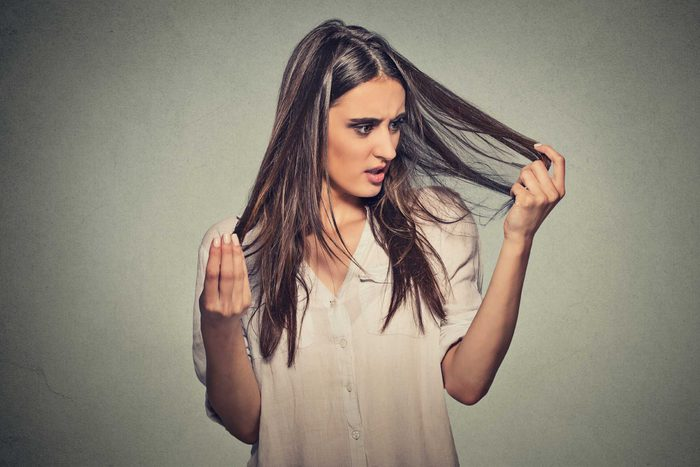 woman looking at her hair in alarm