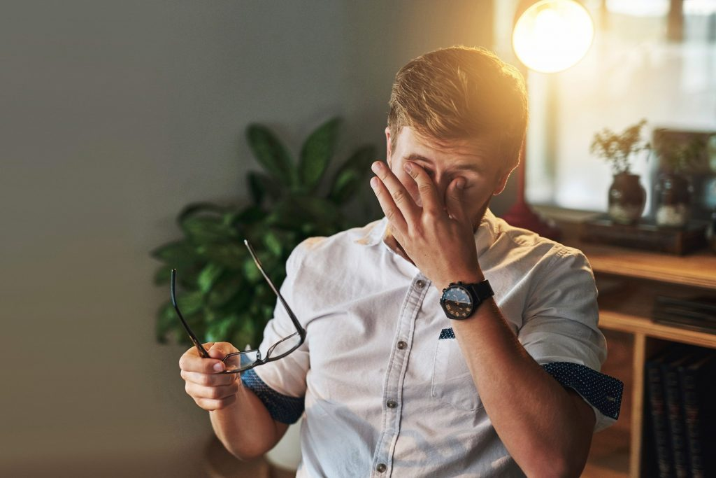 man holding his glasses while he rubs his eyes