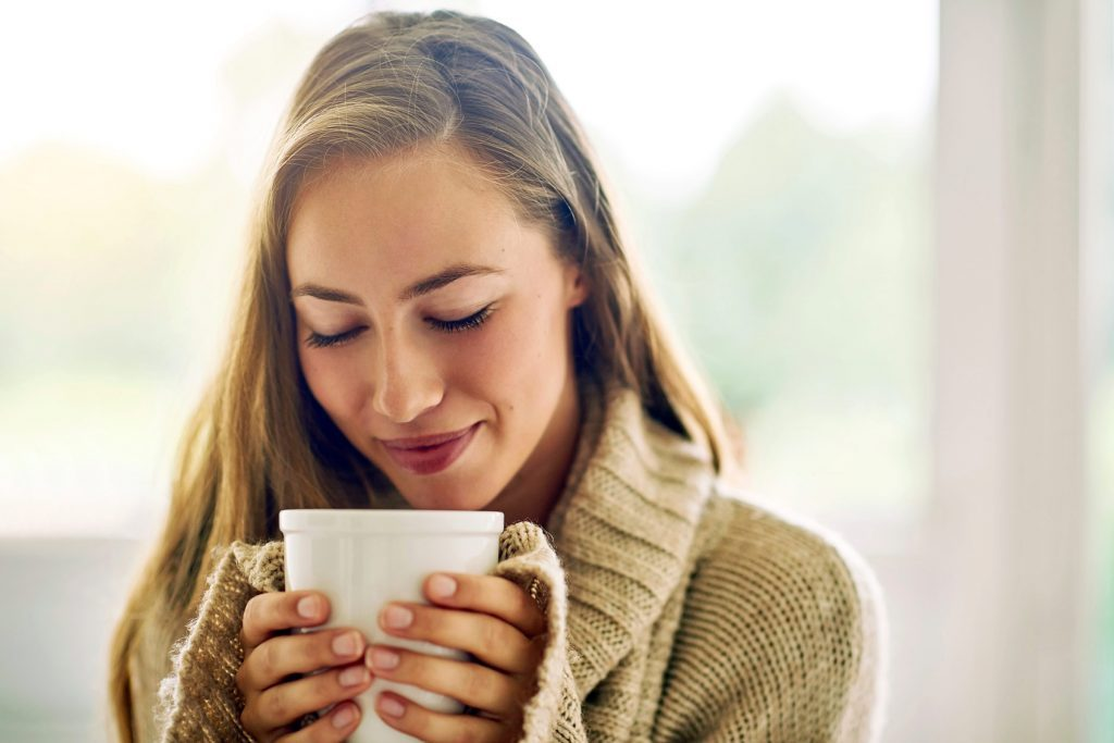 woman holding a cup of coffee with both hands close to her face