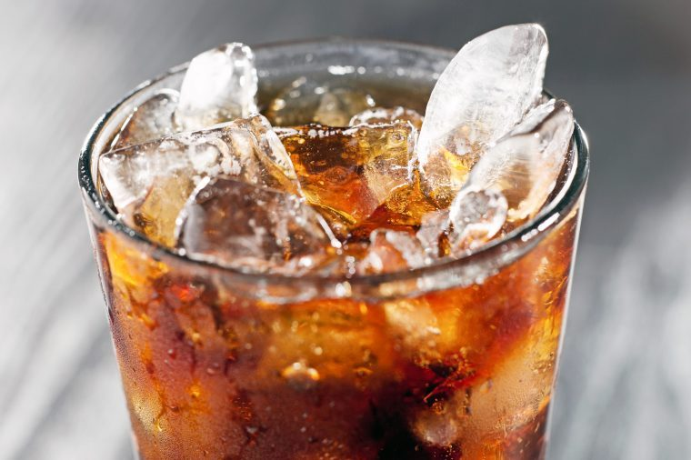 Glass of brown soda with ice.