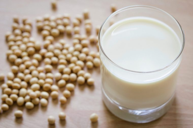 Glass of milk with soybeans on the table.