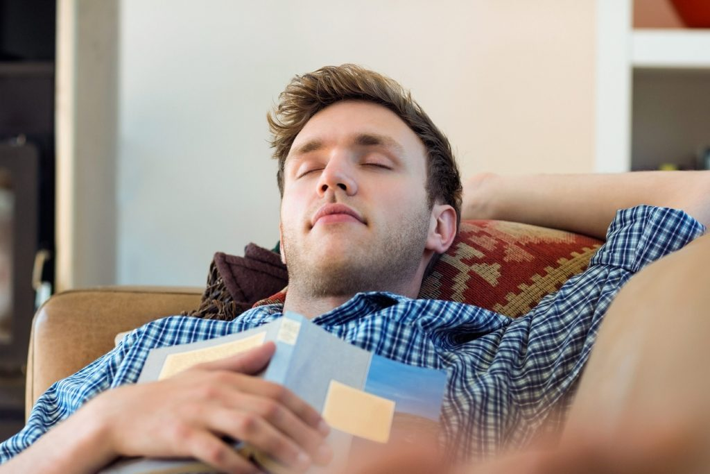 man asleep on his back on a couch, book on his chest