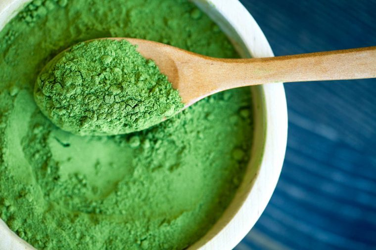Bowl of green spirulina powder and a wooden spoon.