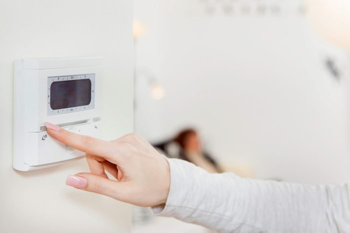 woman changing a thermostat