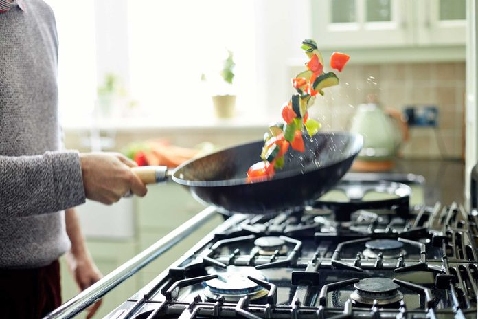 person sauteeing vegetables in a pan over oven