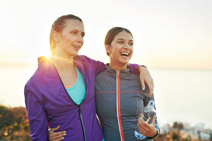 two smiling women in workout clothes, arms around each other, outside