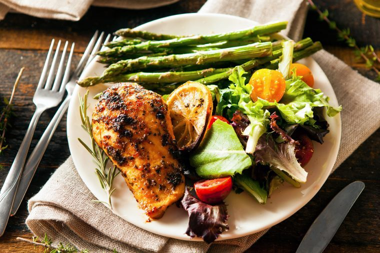 Dinner plate with chicken, asparagus and salad.