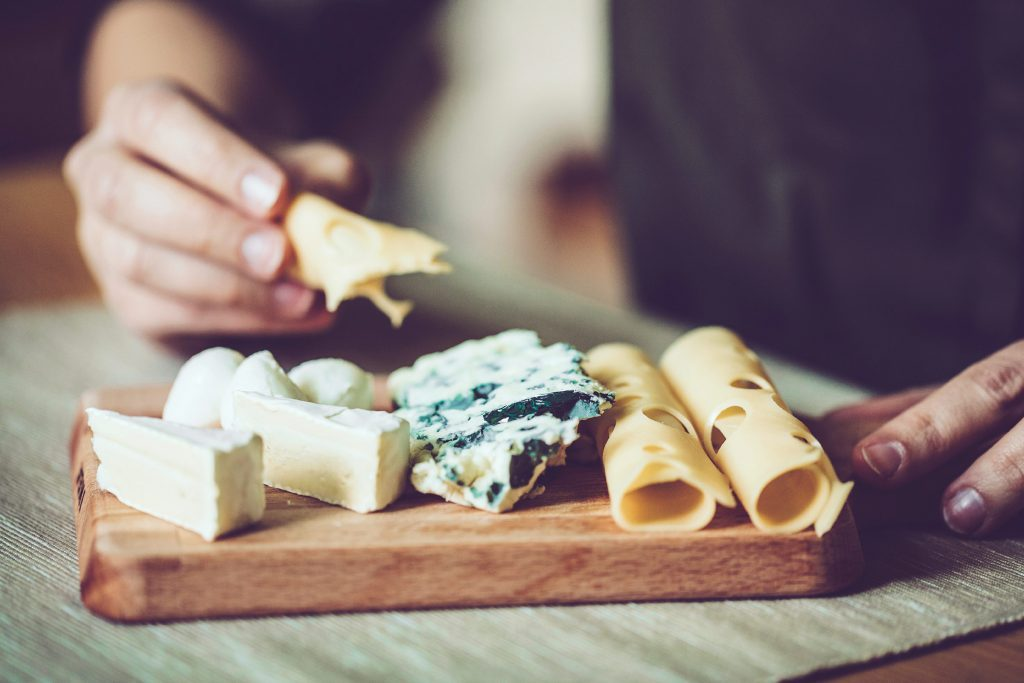 close up of cheese plate; person's hands