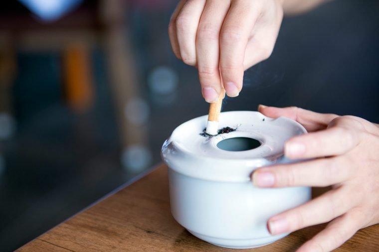 Person stubbing their cigarette out in an ashtray.