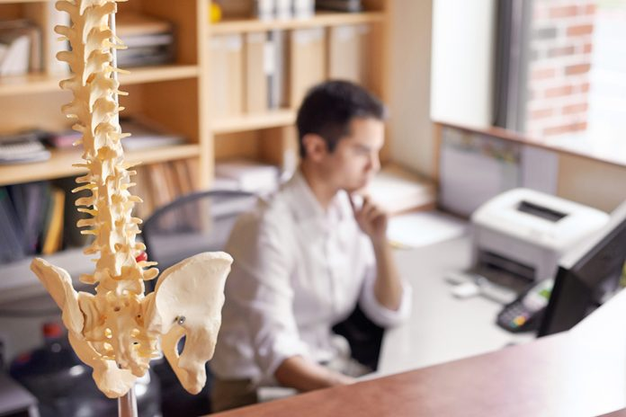 close up of human spine with man in background