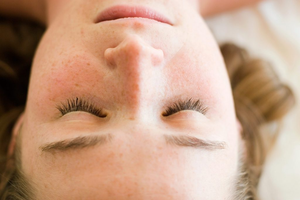 freckled woman with eyes closed lying on her back