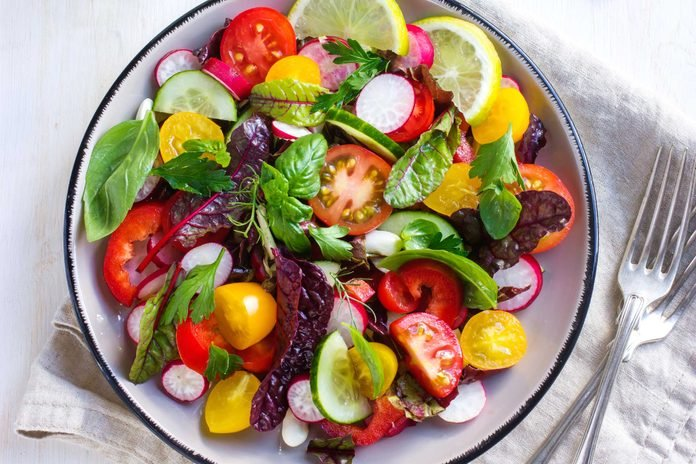 salad with tomatoes, leafy greens, radishes, and lemon slices