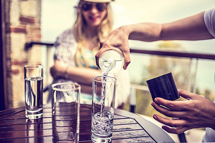 A bartender pouring a glass of water for a patron.