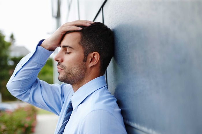 A young male in a shirt and tie looking stressed.