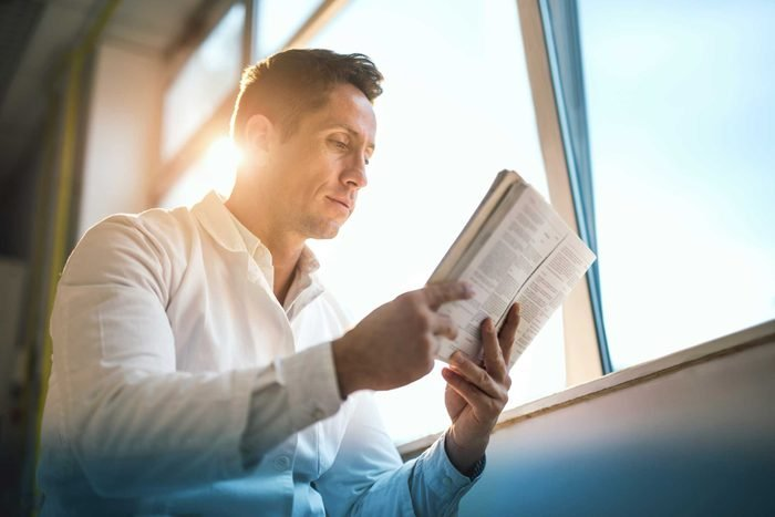 Man near a window reading a book.