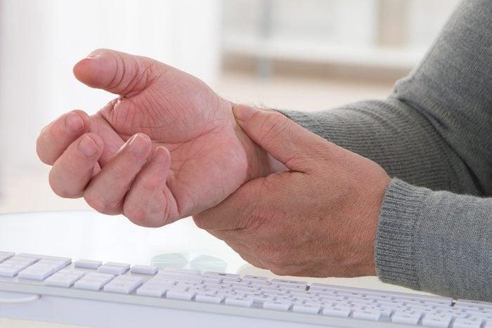 elderly person holding wrist