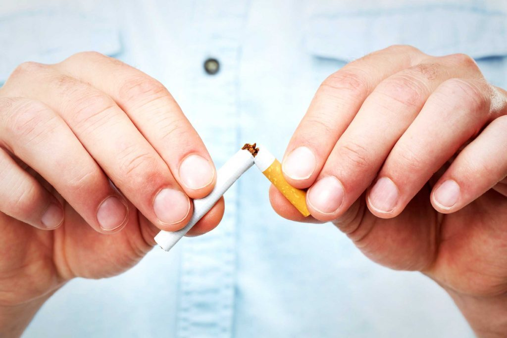 Man snapping a cigarette in half.