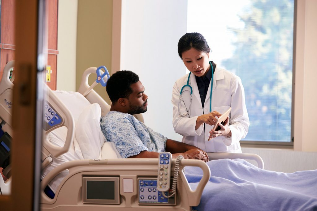Asian doctor at the bedside of an African American patient