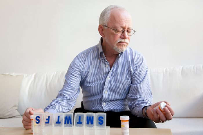 man looking at prescription pills for the week