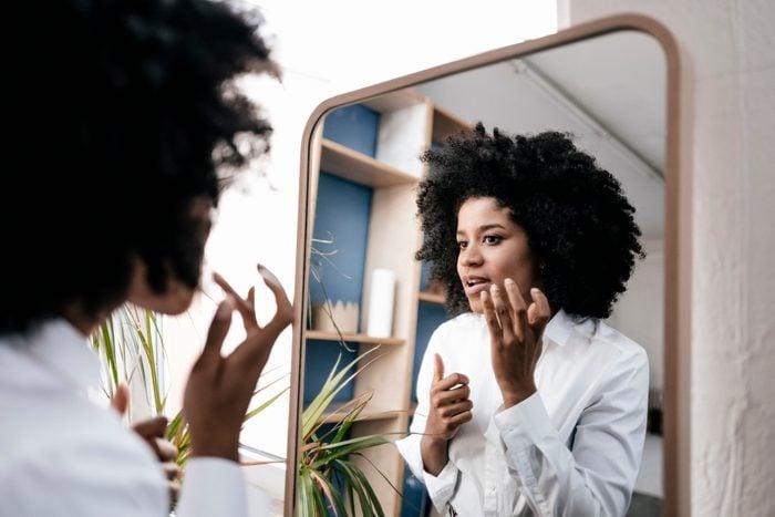 woman applying cream to face