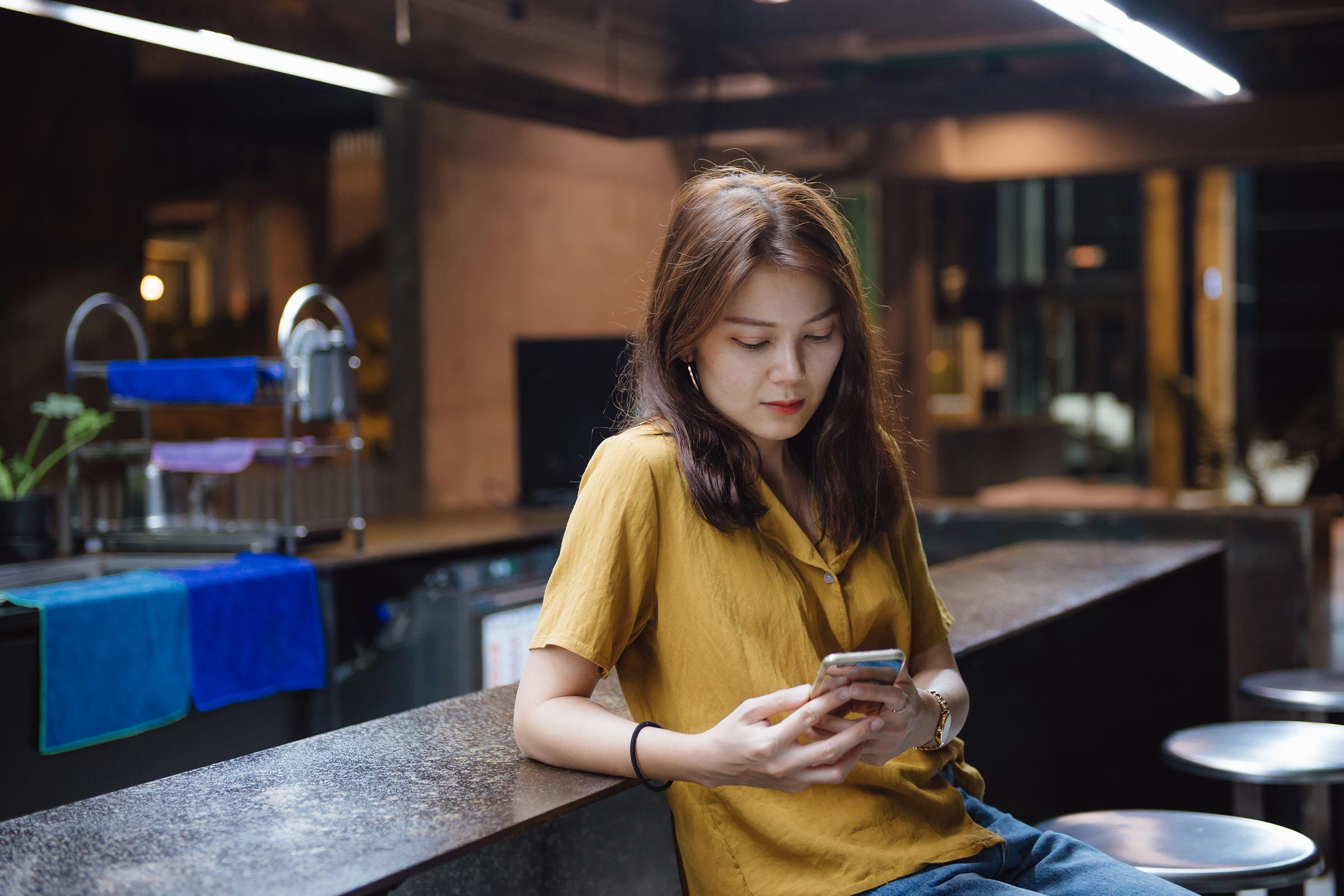 woman alone at bar checking phone