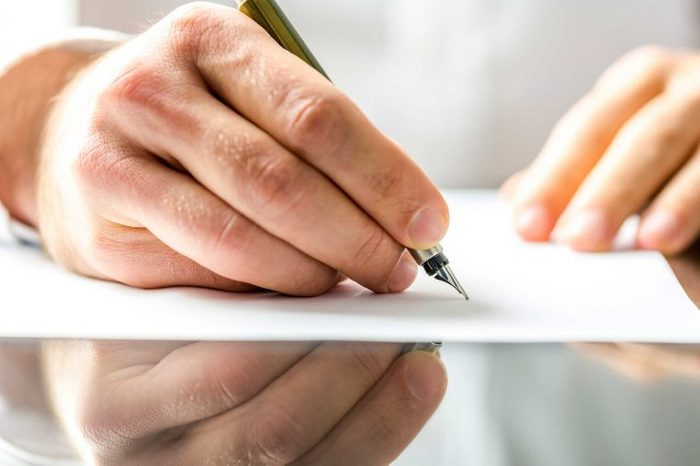 Man's hand using a pen to write on a piece of white paper.
