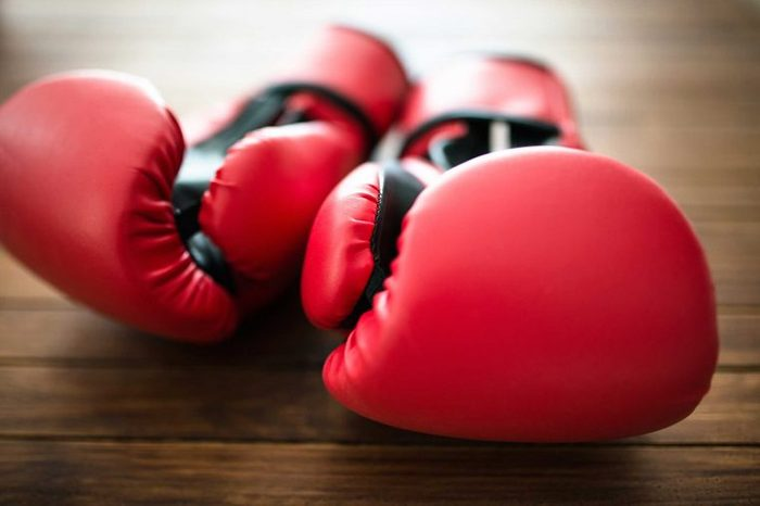 Pair of red boxing gloves on a wooden surface.