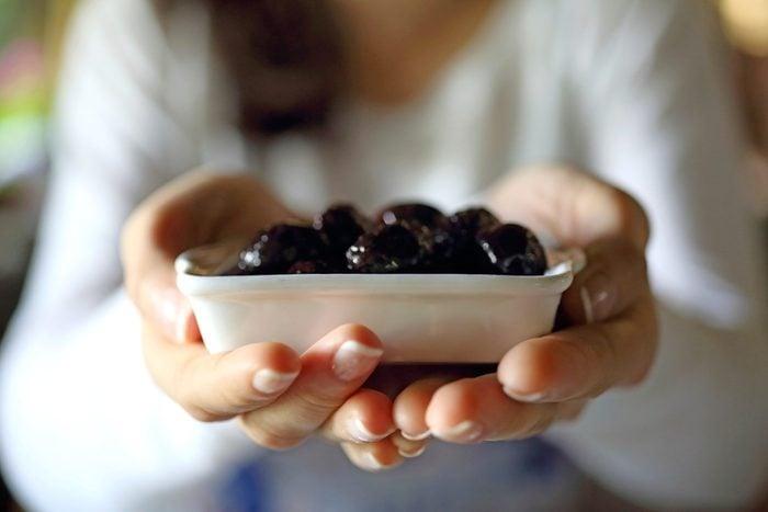 woman holding dish of dark olives