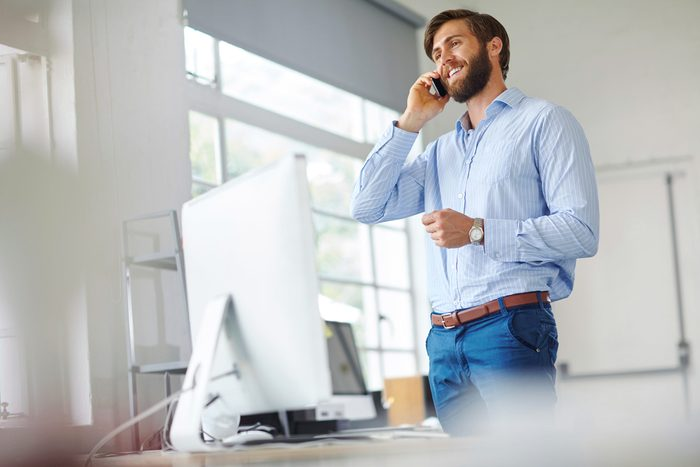 man standing at his desk talking on the phone