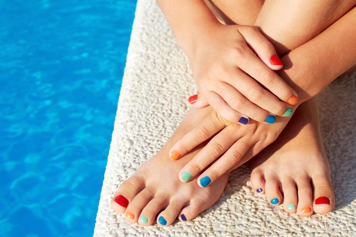 woman with multi-colored fingernails and toenails by the edge of a pool