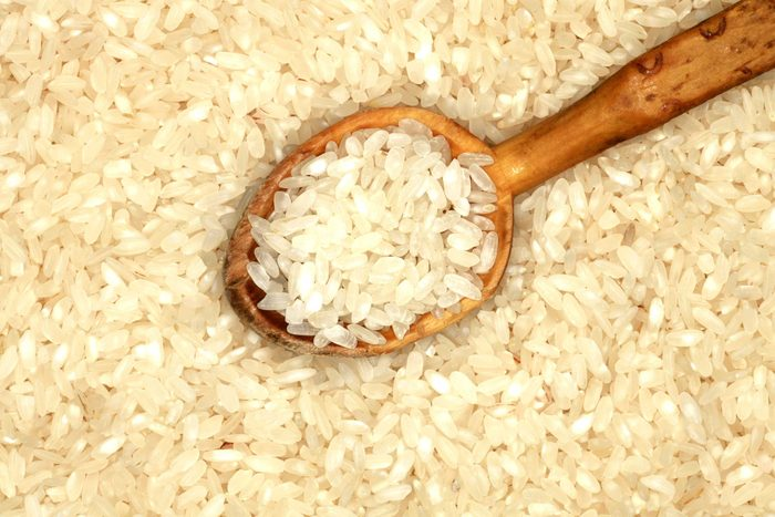 dried white rice grains with a wooden spoon