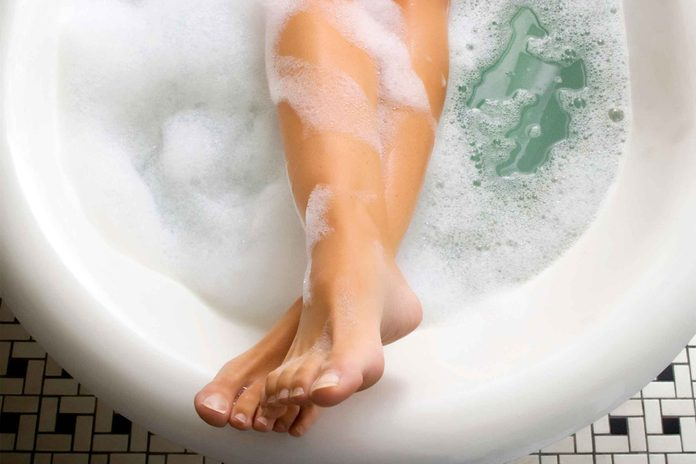 Woman's feet and legs in a bathtub.