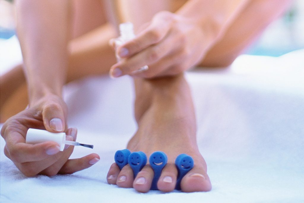 woman giving herself a pedicure