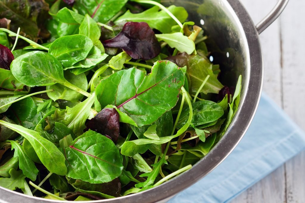 Mixed greens in a colander.