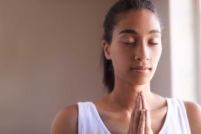 woman holding a meditative pose with hands pressed together