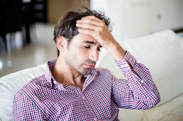 Man sitting on a couch holding his forehead with one hand.