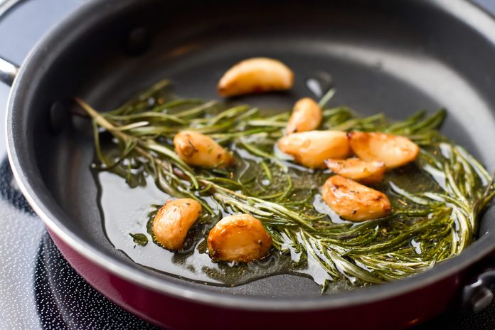 garlic and rosemary cooking in olive oil