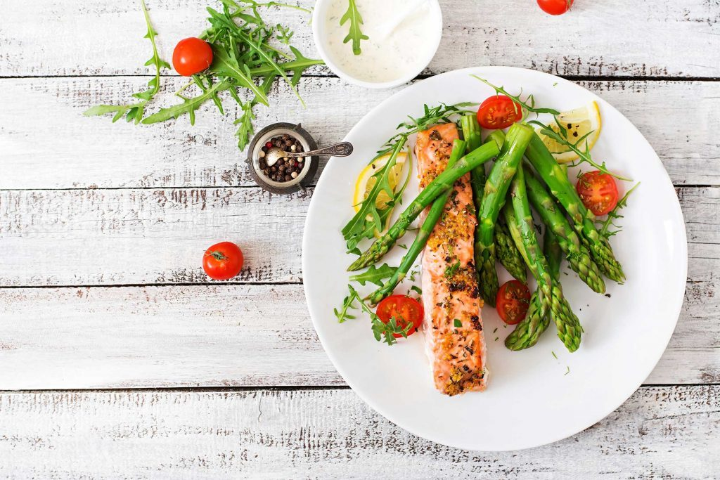 white plate with asparagus, salmon, dill, and lemon slices