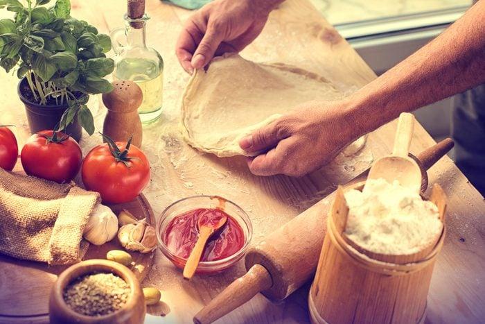 person prepping pizza dough