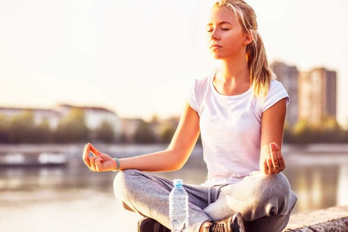 woman in cross-legged yoga pose outside