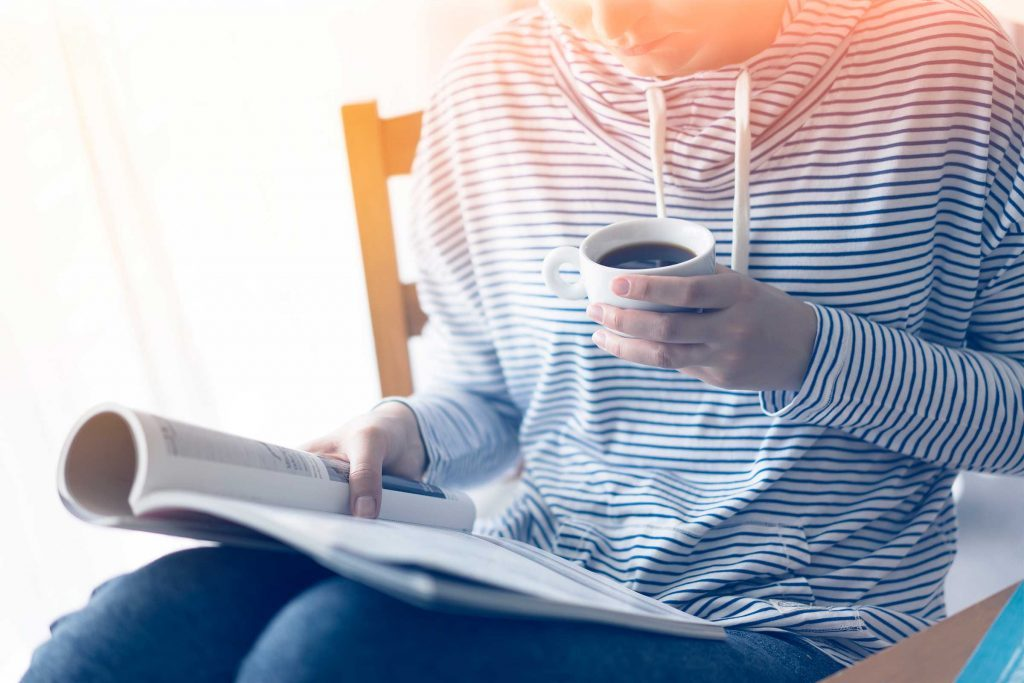 person reading a magazine and drinking a cup of coffee