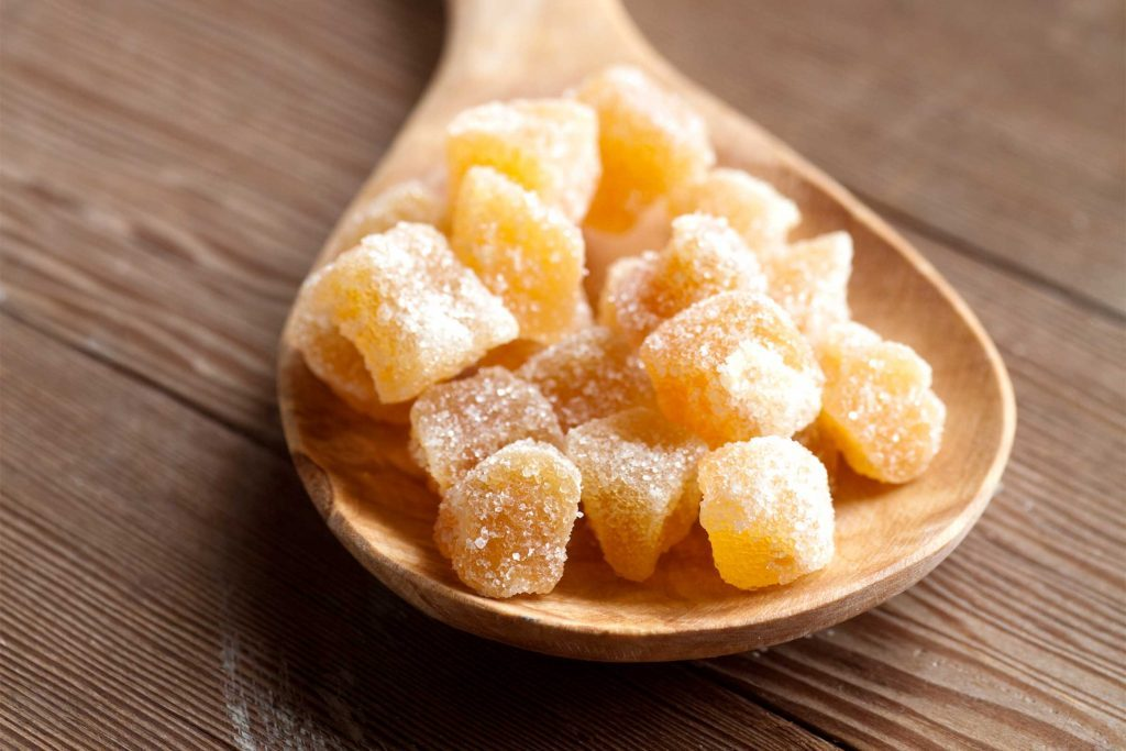 candied ginger cubes on a wooden spoon