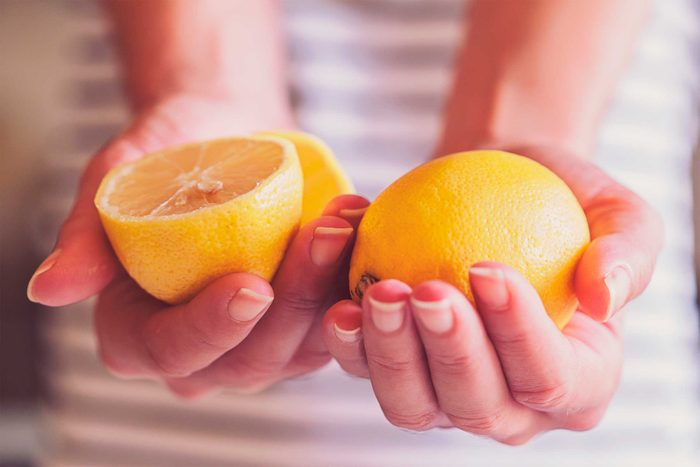 woman holding halves of an orange
