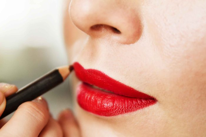 Woman applying red lip liner to red lips.