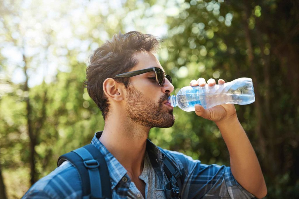 man drinking a bottle of water