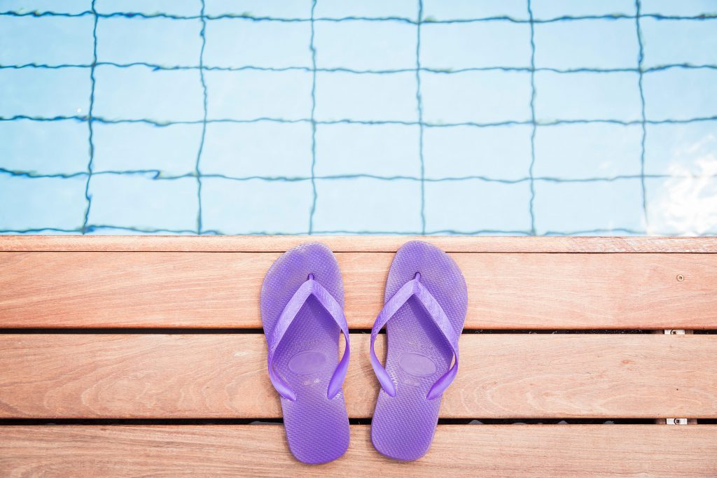 purple flip flops at the edge of a pool