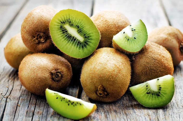 Pile of whole and halved kiwi.