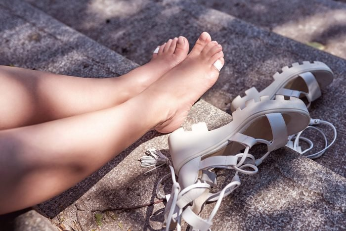 woman's bare feet with Bandaids on the little toes, next to a pair of sandals