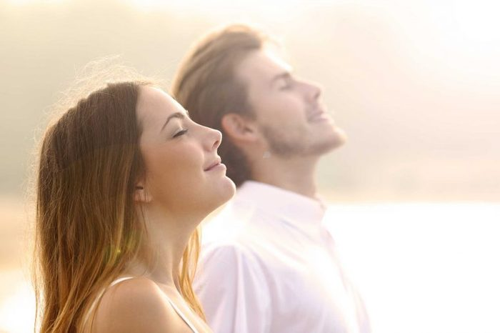 A couple looking happy and meditating in the sunlight.