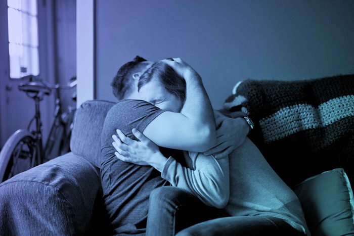 a couple embracing tightly on a couch